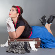 Funny beautiful pinup girl lying on overfilled suitcase — Stock Photo #23368328
