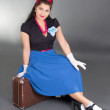 Young attractive pinup woman sitting on retro suitcase — Stock Photo #23368364