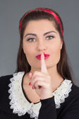 Portrait of young attractive maid with finger on her lips — Stock Photo