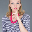 Attractive pinup girl in striped dress with finger on lips - Stock Photo