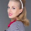 Young attractive blondie pinup girl in striped dress - Stock Photo