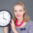 Attractive pinup girl in striped dress with clock - Stock Photo