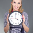 Dreaming pinup girl in striped dress with clock - Stock Photo