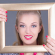 Attractive blondie pinup girl in striped dress with photo frame - Stock Photo