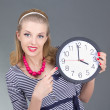 Pinup girl in striped dress holding the clock — Stock Photo