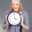 Dreaming pinup girl in striped dress with clock over grey - Stock Photo