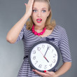 Shocked pinup girl in striped dress holding the clock - Stock Photo