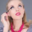 Beautiful woman applying mascara make up on eyes - Stock Photo