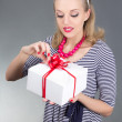 Attractive pinup girl in striped dress opening gift - Stock Photo