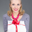 Pinup woman in striped dress giving a present - Stock Photo