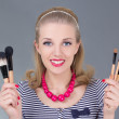Portrait of young pinup woman with make up brushes — Stock Photo #23638175