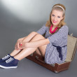 Pinup woman sitting in big brown retro suitcase — Stock Photo #23638179