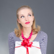 Dreaming pinup woman in striped dress giving a present - Stock Photo