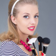 Young pinup woman with make up brushes - Stock Photo