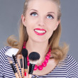 Young dreaming pinup woman with make up brushes - Stock Photo