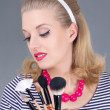 Dreaming pinup woman with make up brushes - Stock Photo