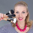 Pinup woman with make up brushes - Stock Photo