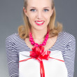 Attractive pinup woman in striped dress giving a present - Stock Photo
