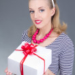 Attractive pinup girl in striped dress with gift - Stock Photo