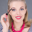 Young beautiful woman applying mascara make up on eyes - Stock Photo