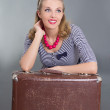 Beautiful pinup woman sitting with brown retro suitcase - Stock Photo