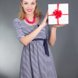 Attractive pinup woman in striped dress with gift over grey — Stock Photo #23638375