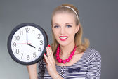 Attractive pinup girl in striped dress with clock — Stock Photo