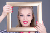 Attractive blondie pinup girl in striped dress with photo frame — Stock Photo