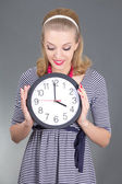 Dreaming pinup girl in striped dress with clock over grey — Stok fotoğraf