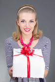 Pinup woman in striped dress giving a present — Stock Photo