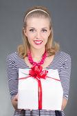 Szałowy kobieta w paski sukienkę dając prezent — Zdjęcie stockowe