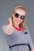 Young beautiful pinup girl in sunglasses thumbs up — Stock Photo