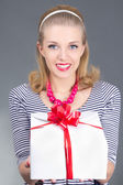 Attractive pinup woman in striped dress giving a present — Stock Photo