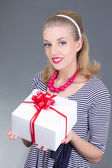 Attractive pinup girl in striped dress with gift — Stock Photo