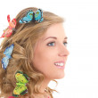 Portrait of young beautiful blond with butterflies in her hair — Stock Photo