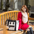 Redhaired woman crossing sitting on the bench in park — Stock Photo