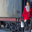 Royalty-Free Stock Photo: Redhaired woman in red coat and vintage train