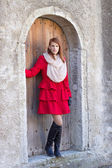 Beautiful redhaired woman posing in front of the old door — Stock Photo