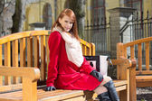 Redhaired woman crossing sitting on the bench — Stock Photo