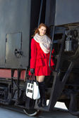 Beautiful woman in red coat and vintage train — Stock Photo