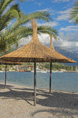 Straw sunshades and palm leafs on the beach in Montenegro — Stock Photo