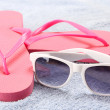 Red flip flops and sunglasses over towel — Stock Photo