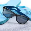 Stock Photo: Flip flops and sunglasses on the towel