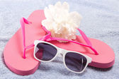 Red flip flops, sunglasses and flower over towel — Stock Photo