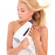 Young attractive woman drying her hair with hairdryer — Stock Photo