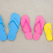 Colorful flip flops on sandy beach — Stock Photo