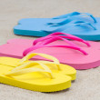 Selection of rubber flip flops in multiple colors on beach — Stock Photo