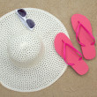 Pink flip flops, sunglasses and hat on sandy beach — Stock Photo #27770123