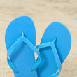 Bright blue rubber flip flops on sand — Stock Photo #27770163