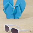 Blue rubber flip flops and sunglasses on the sand — Stockfoto